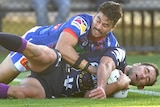 A Melbourne Storm NRL player is tackled by a Newcastle Knights opponent while holding the ball.