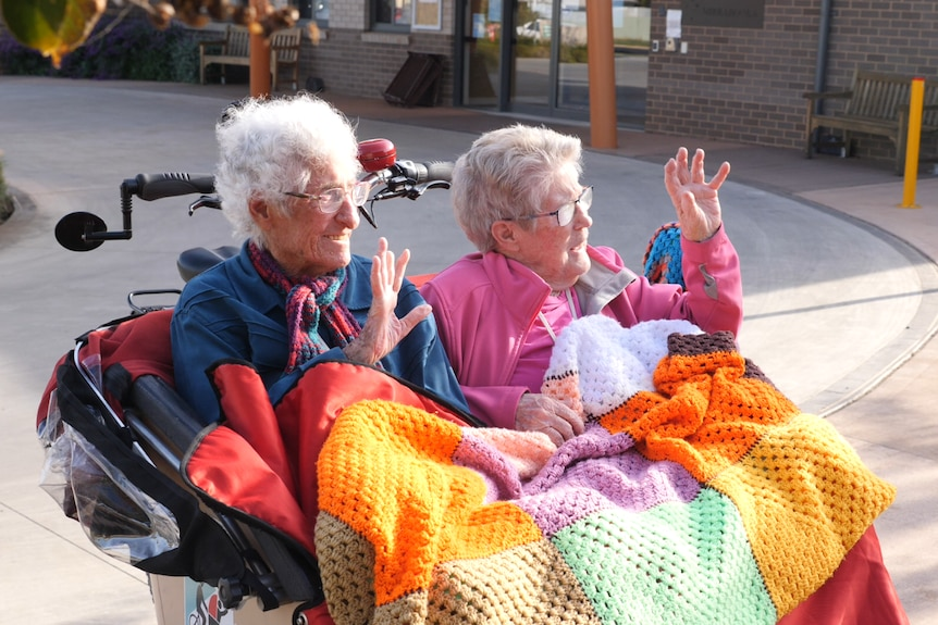 Two elderly women sitting in the front of a trishaw waving with a coloured blanket on their lap.
