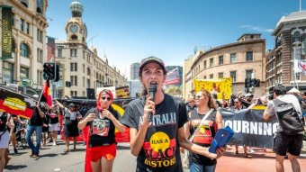 """A woman at the head of a march with a microphone wears a t-shirt that reads """"Australia has a black history""""."""