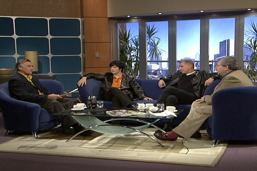 Cassidy sitting on chair and panel on couch on original Insiders set.
