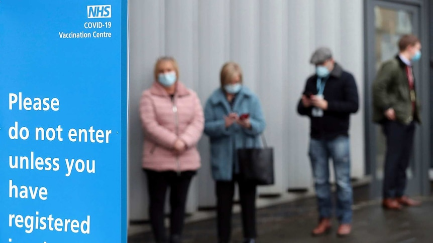 people stand in line wearing masks as a sign reads please do not enter unless you have registered in advance