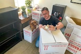Paul Menz packing boxes, with his dog standing on one of the boxes.