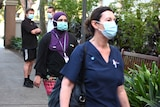 Two women wearing masks walk past two men wearing masks.