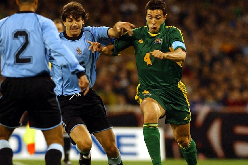 A Socceroos midfielder goes full tilt at the ball while a Uruguayan defender tries to pull him back.