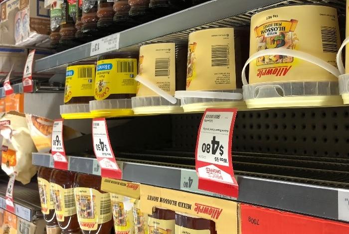 Allowrie honey stacked on shelves in Woolworths, alongside Capilano honey.