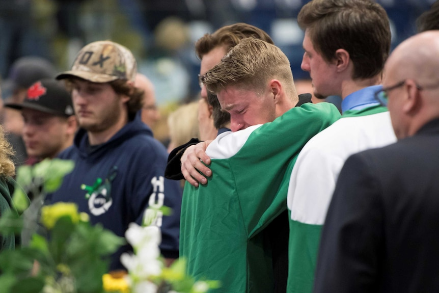 Mourners comfort each other during a vigil at the Elgar Petersen Arena
