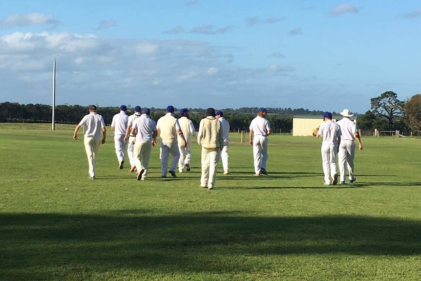 A group of cricketers walk onto the field