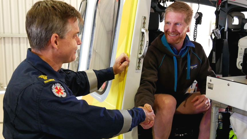 A man sitting inside a helicopter shaking the hand of a paramedic in uniform