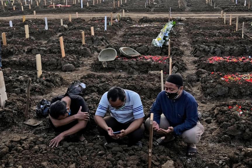 Los hombres rezan mientras su familiar está enterrado en un cementerio