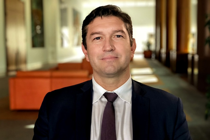 Man in suit and tie with black hair sits smiling with couches and formal walkway behind him