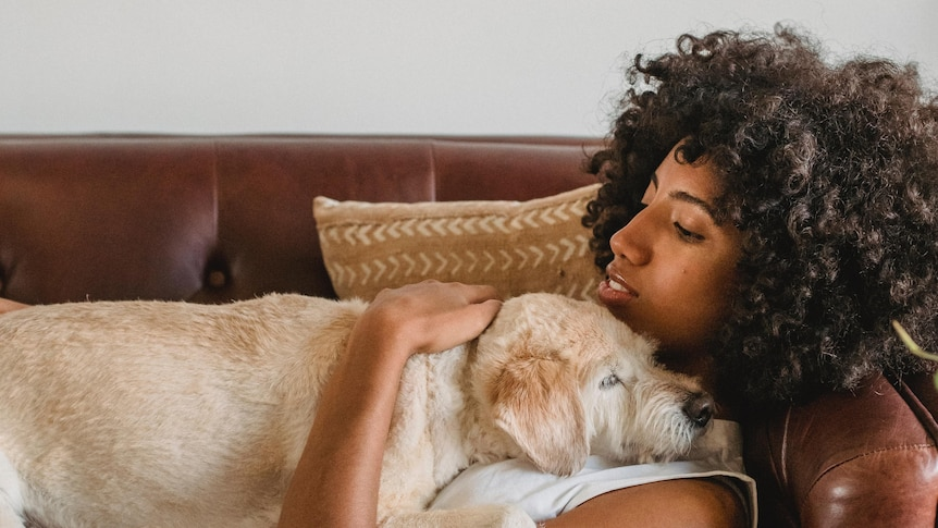 Woman lays on couch hugging her dog