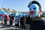 A man wearing a mask with the East Turkistan and Chinese flags