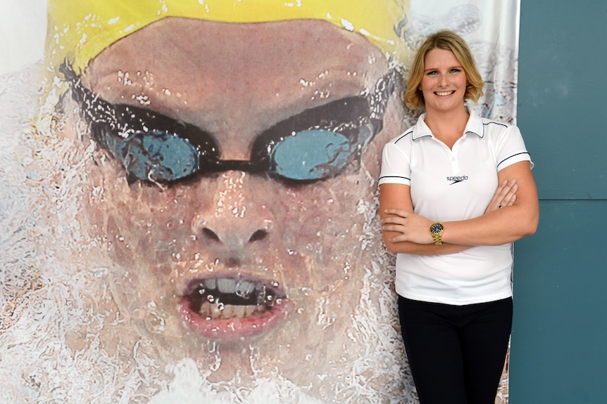Female swimmer standing in front of a mural of her with her arms folded and smiling.