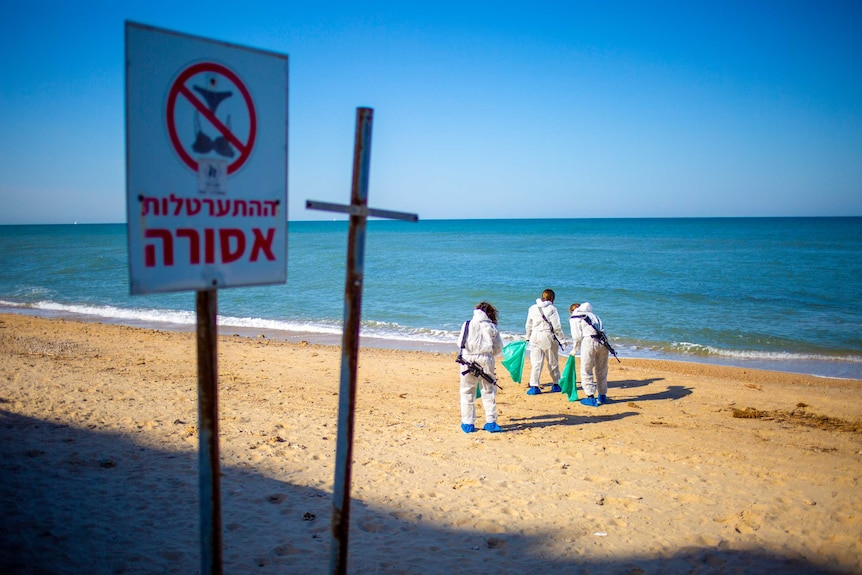 Three people in protective suits with rifles slung over their shoulders standing on a beach with plastic bags