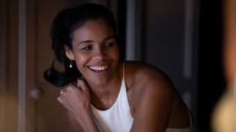 The actor Zahra Newman in the film Long Story Short, smiling in a white dress