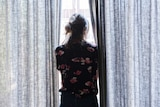 A woman stands looking out a bright window, next to her on either side are patterned floor to ceiling curtains.