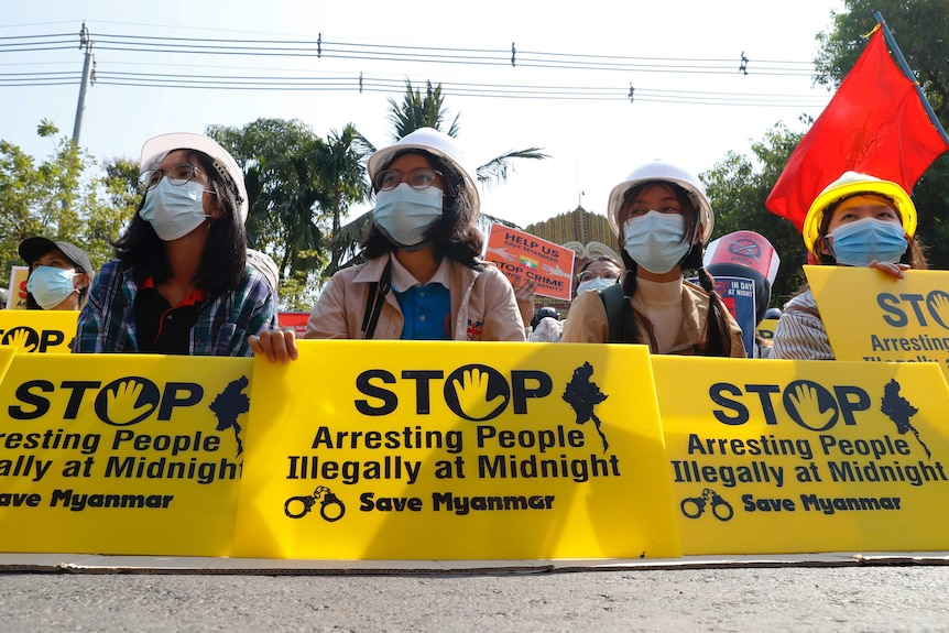 """Four young women in face masks hold yellow signs reading: """"Stop arresting people illegally at midnight save Myanmar""""."""