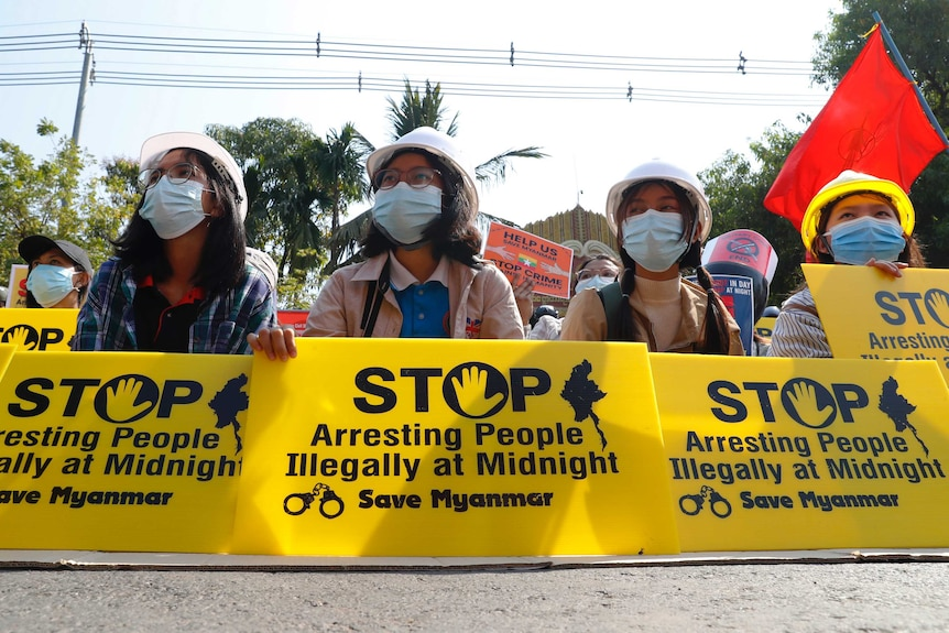 "Mandalay University graduates hold posters that say ""Stop Arresting People illegally at midnight"""