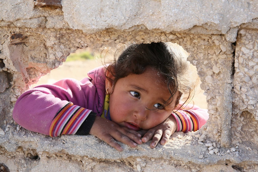 A little girl stares through a hole in a stone fence.