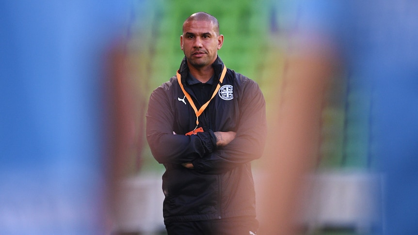 Patrick Kisnorbo watches training with two players standing blurred in the foreground
