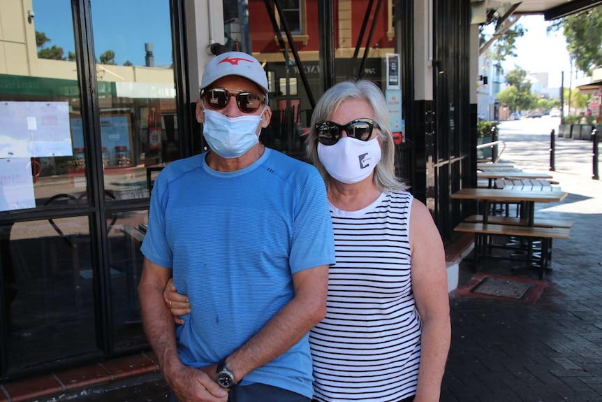 A man and a woman wearing masks pictured in an outdoor alfresco area