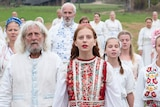 A group of people in white clothes covered in colourful flowers stare mournfully into the distance.