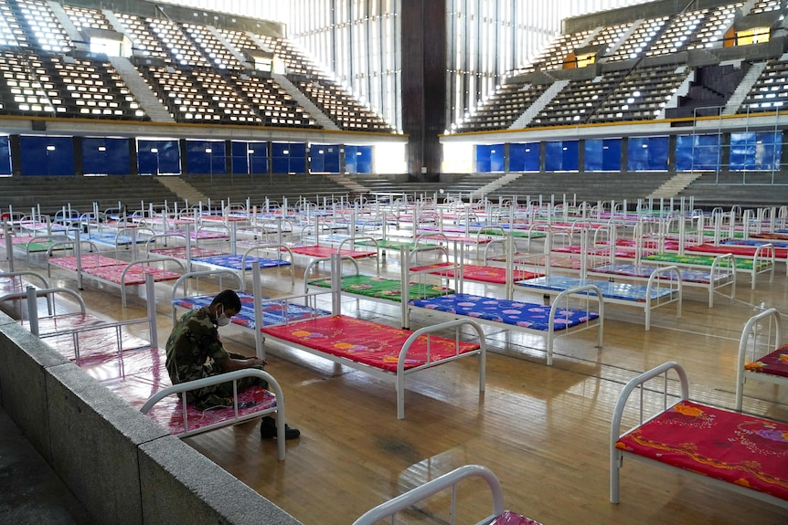 A man sits in a gymnasium, which has been filled with hospital beds