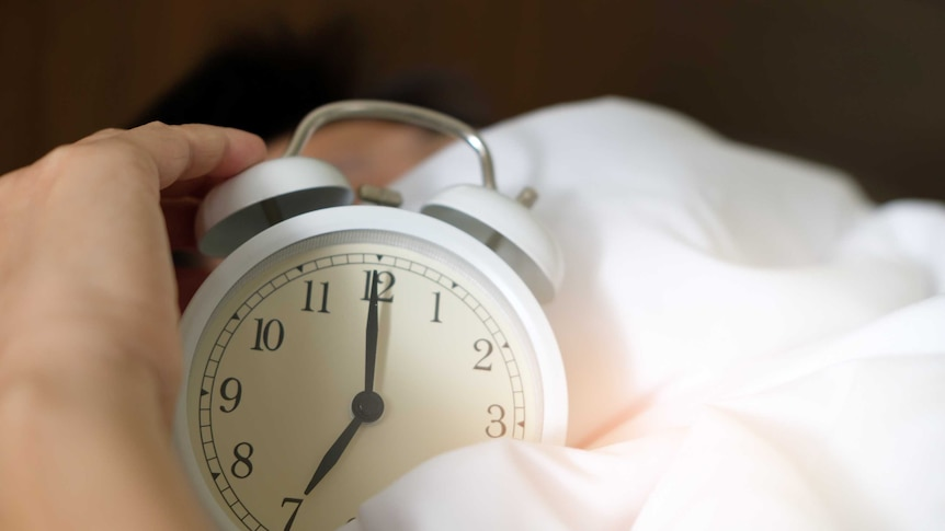 a hand picks up an old-fashioned alarm clock