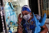 """A woman adjusts her protective goggles as she leaves after visiting an altar to the """"Santa Muerte,"""" or Death Saint."""