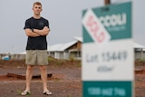 A 24-year-old man stands with his arms folded, smiling on his newly purchased block of land. A sold sign is at the forefront.