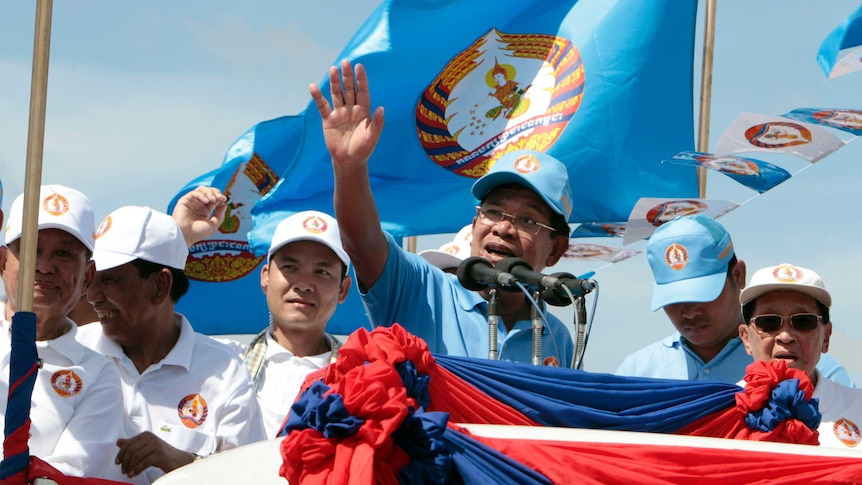 Cambodian Prime Minister Hun Sen waves to supporters as he speaks at a podium during an election campaign rally.