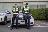 Senior Constable Steve Allison and Constable Kur Thiek standing in front of a police car.