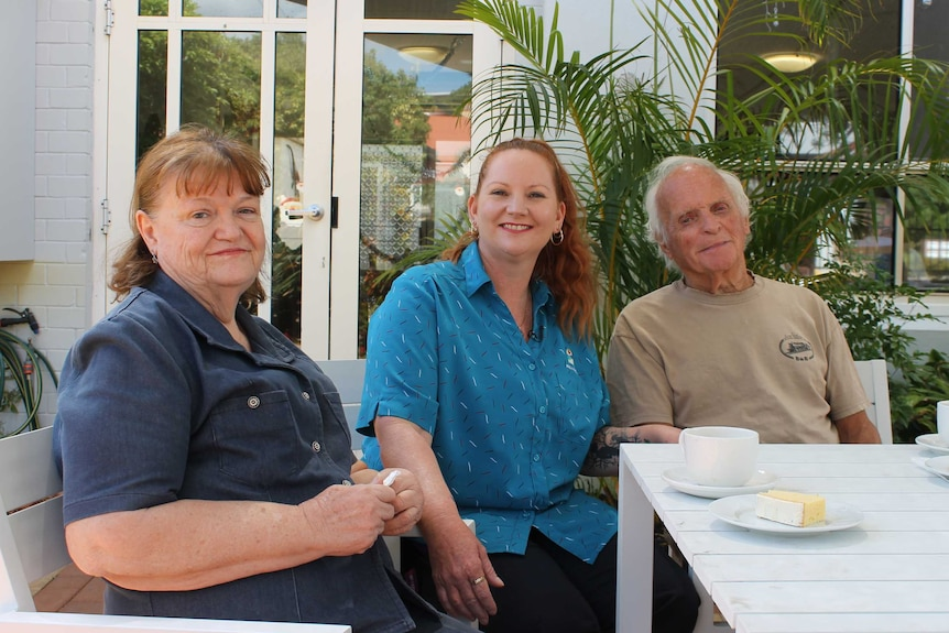 carer sits at table with an elderly man and woman