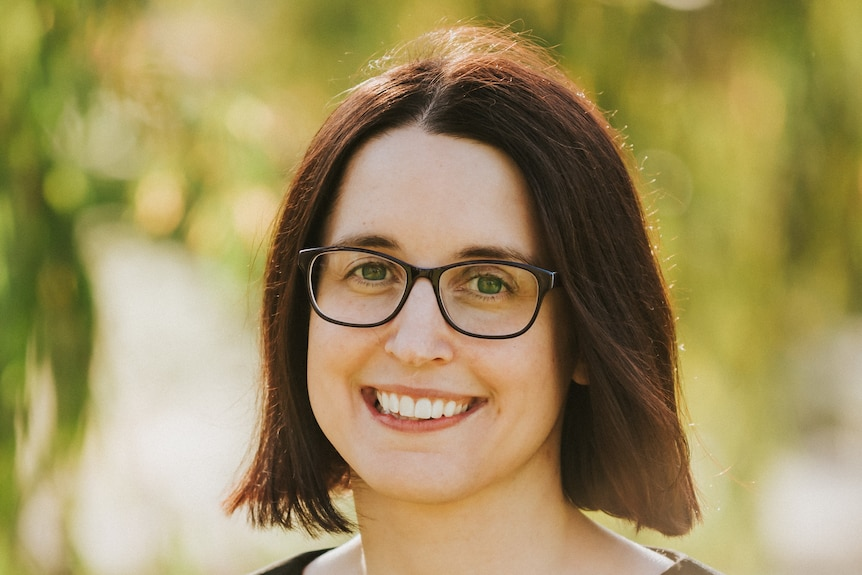 A bespectacled woman smiles as she poses for a portrait photograph in the sunshine.