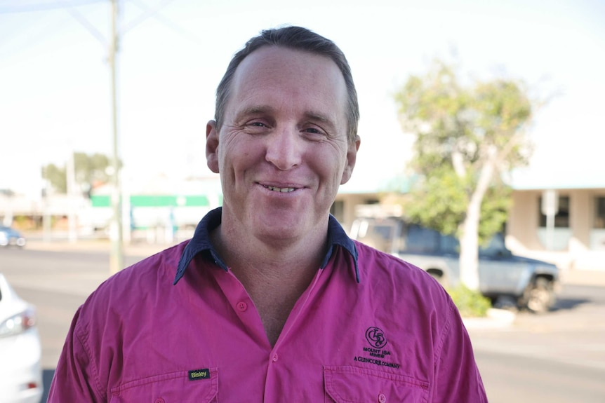 A man in a pink high visibility work shirt smiles at the camera.