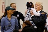 Donald Trump lifts up a little girl wearing pyjamas at a hurricane relief centre, while Melania Trump smiles