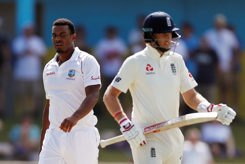 Shannon Gabriel looks to his left at Joe Root, who has his backed turned to Gabriel.