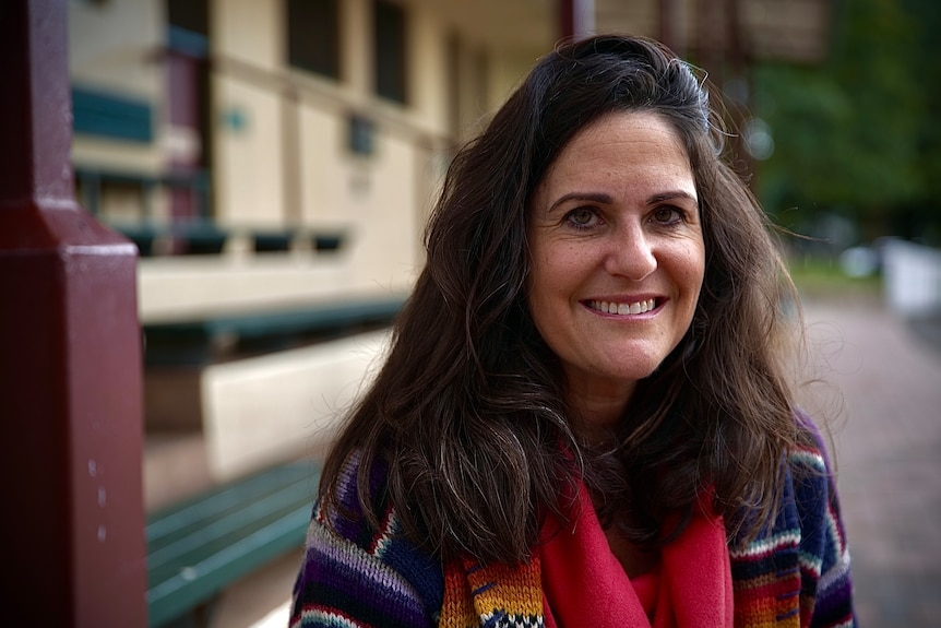 Woman with brown brown hair smiling.