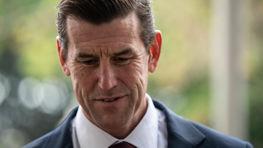 A man in a suit looking down