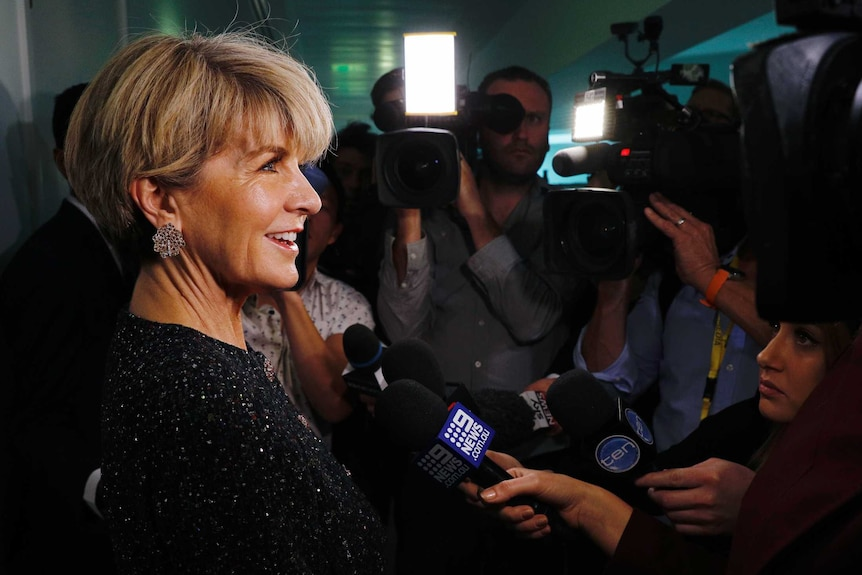 Julie Bishop, in a sequinned top and dazzlingly sparkly earrings, is surrounded by journalists with cameras and microphones.