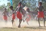 Aboriginal children in red and wearing headbands dance at Barunga