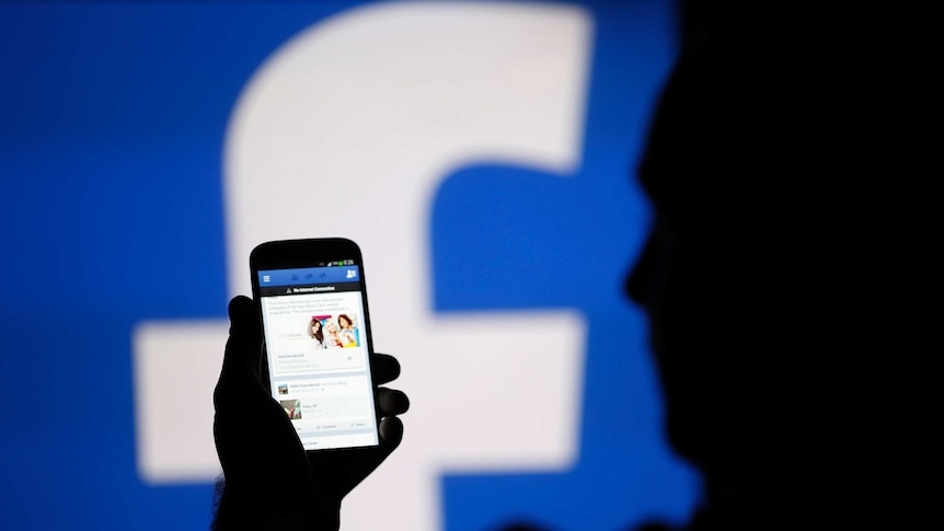 A man is silhouetted against a video screen with an Facebook logo as he poses with a smartphone