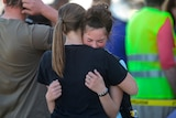 Two young girls embrace after a school shooting.