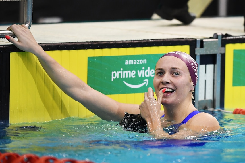 A smiling Ariarne Titmus puts her hand to her face in delight after winning a race at Australia's Olympic swim trials