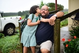 A little girl kissing a man in front of a house