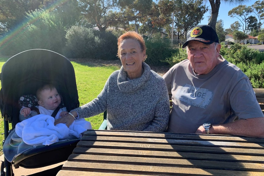Ursula Steinberner and Leon Sharp sitting at a park table with one of their grandchildren in a pram.