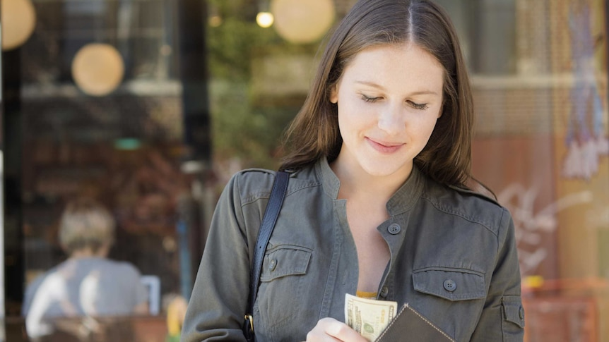 A woman looking please with herself as she puts money in her wallet.