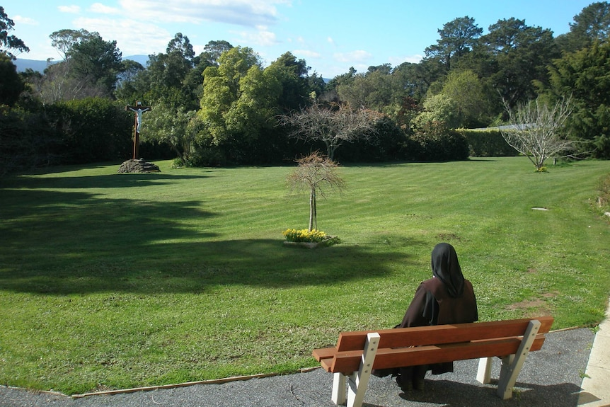 A nun sits outside on a seat looking into a garden.