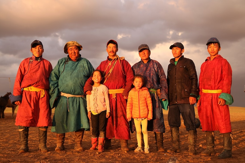 Six Mongolian men stand in the Gobi Desert in robes with two Mongolian girls.