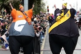 A composite image places a Giants fan and a Richmond fan, both in balloon suits, side by side.